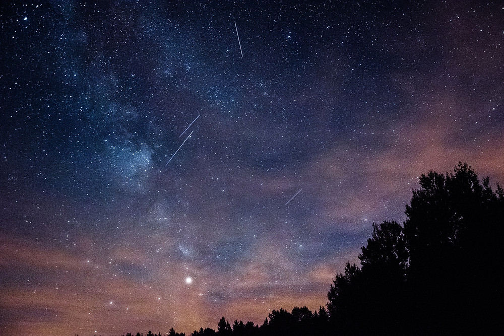 The night sky is littered with meteors streaking across in front of the Milky Way