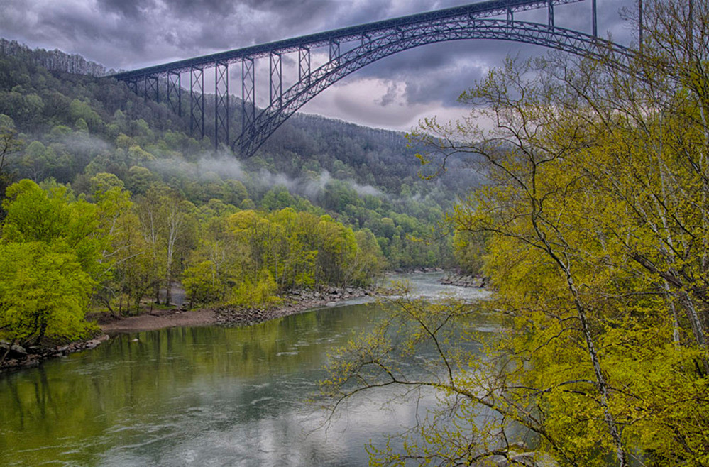 Magnificent cloudy skies lurk ominously over an enormous arched bridge spanning New River Gorge in America's newest State Park, West Virginia