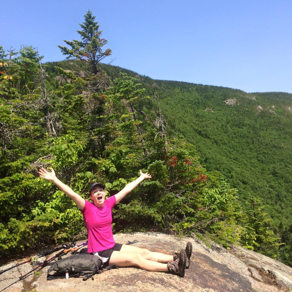 a triumphant woman wearing pink with her arms outstretched, excited to have reached the summit of one of the taller peaks of White Mountains National Forest in New Hampshire. The mountainside is lush with green vegetation