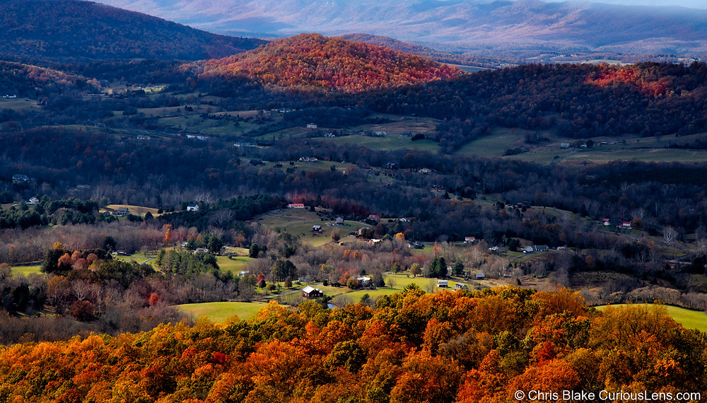 a panoramic view of the Shenandoah Valley in Virginia during the Autumn. Leaves are changing colors brilliantly on the hillsides, dotted by houses and farms