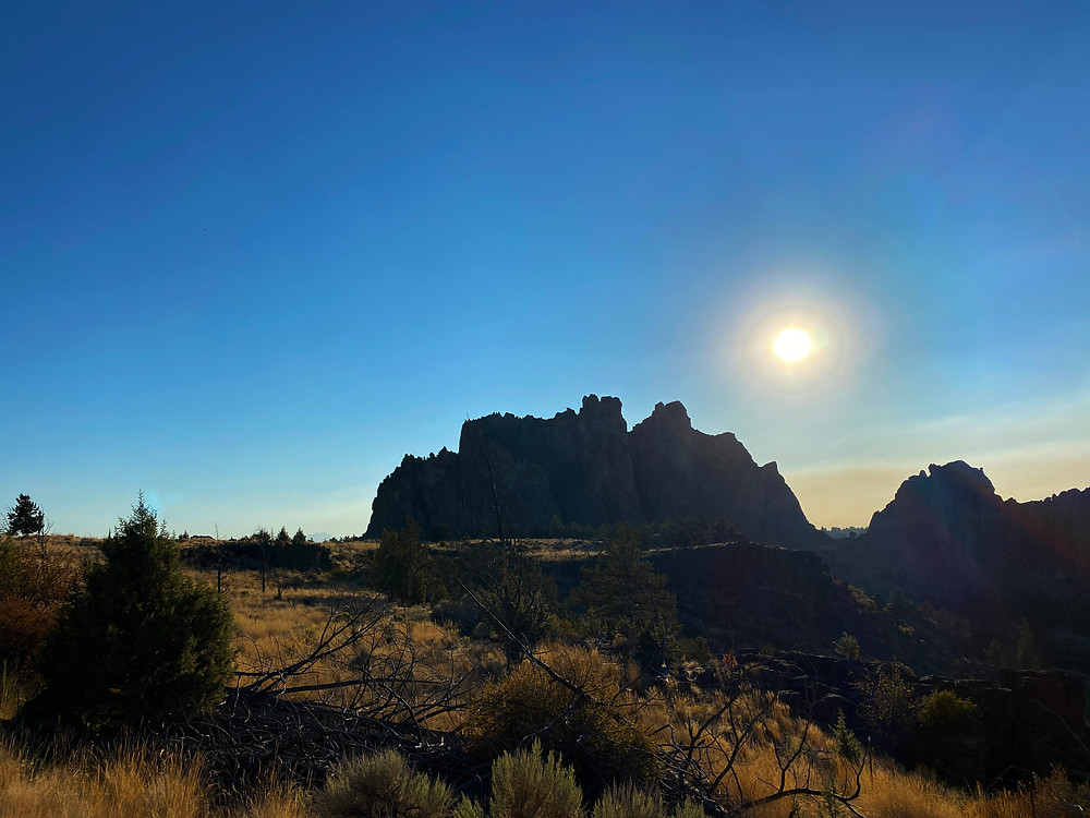 craggy Smith Rock looms over a high desert landscape, browned by the hot sun burning overhead
