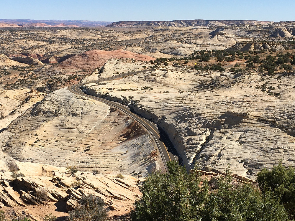 a road winds through the red and brown sandstone rock formations of Grand Staircase Escalante National Monument in Southern Utah