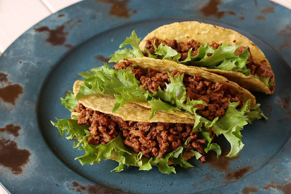 Tacos conditi con carne piccante e foglie di lattuga verde
