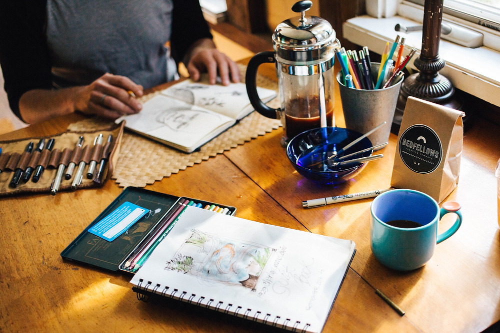 Person with coffee and sketch pad