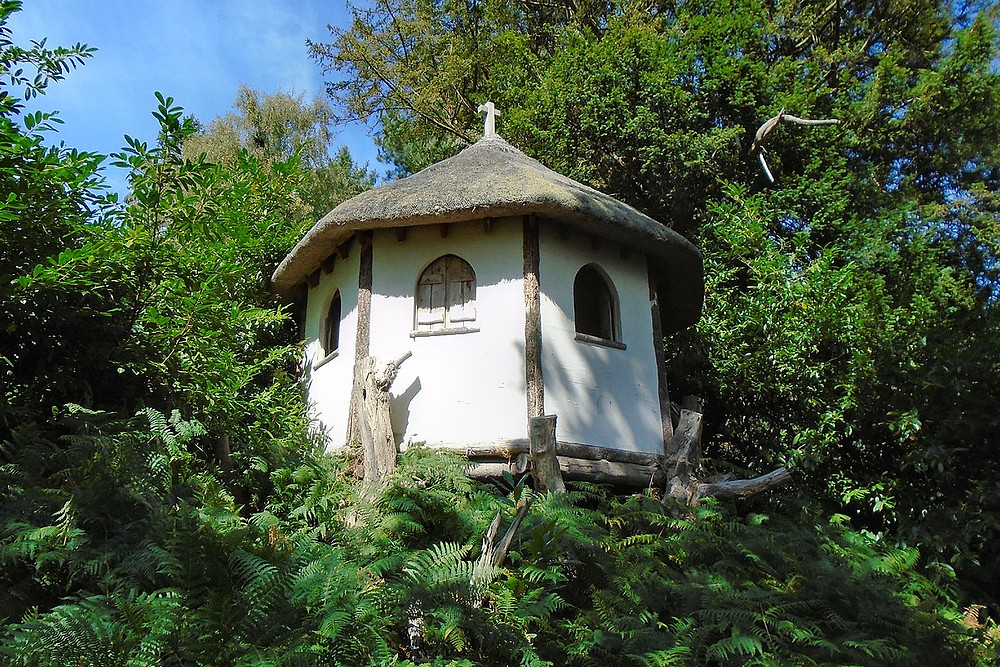 Whimsical folly with thatched roof raised on gnarled wooden branches