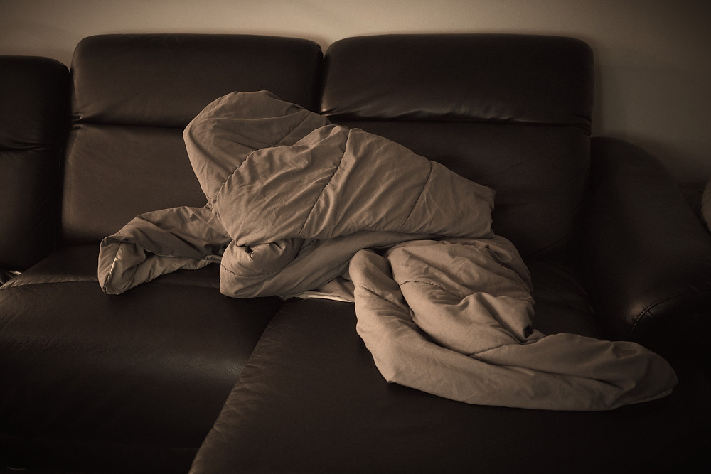Person curled up in duvet on sofa