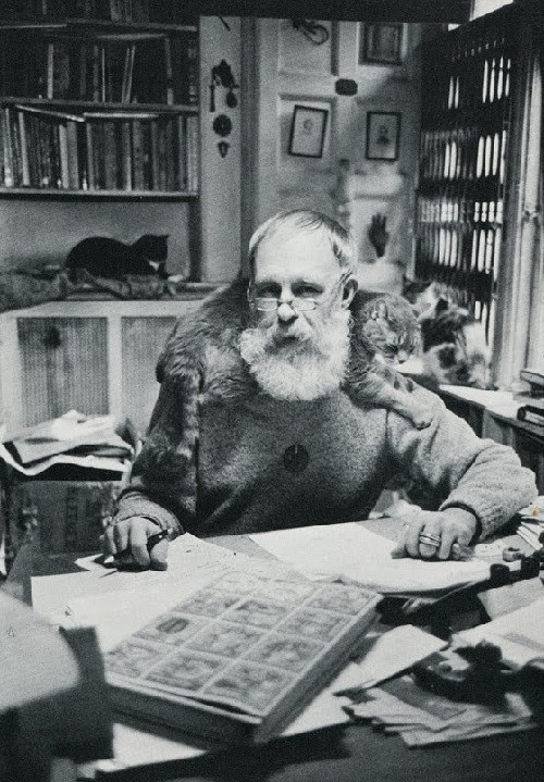 Black and white photograph of artist edward gorey surrounded by cats in his office