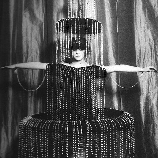 A black and white photograph of The Marchesa Luisa Casati with a fountain like beaded dress