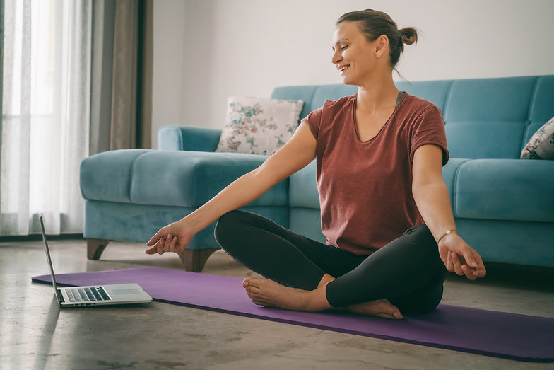 Attractive young woman doing yoga stretching yoga online at home. Self-isolation is benefi