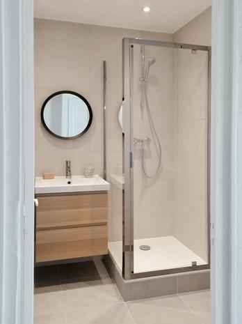 vue de la salle de bain meuble bois ikea avec vasque encastrée et mitigeur chrome miroir rond carrelage pamesa de chez Richardson cabine de douche et faux-plafond