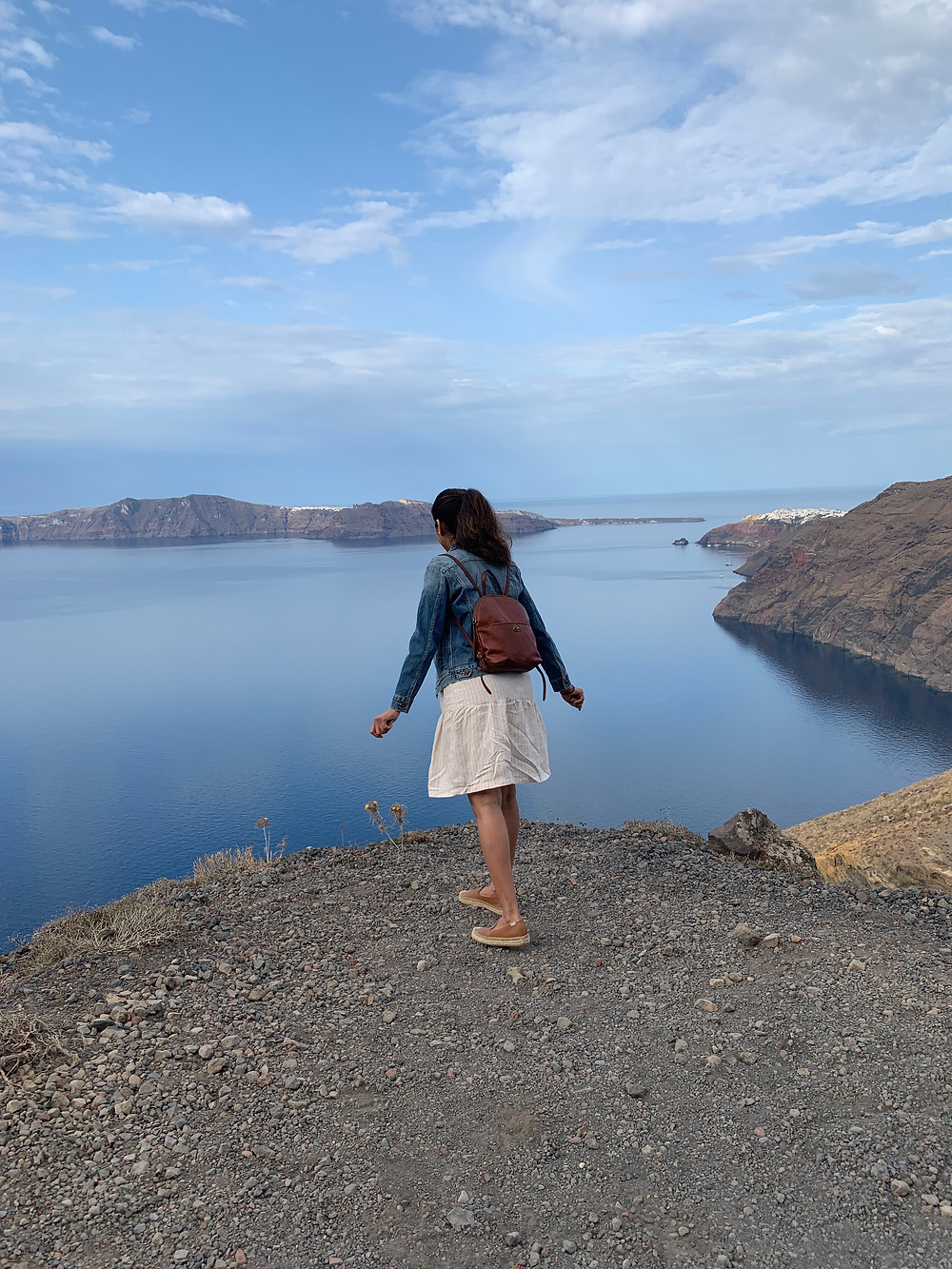 Vaishali Patel of Sanskar Teaching looking over the edge of a steep cliff on the path between Oia and Fira in Santorini Greece