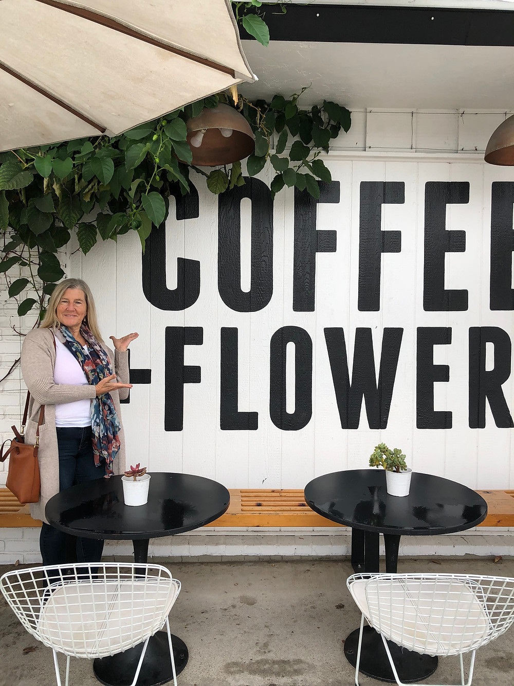 Siri Kay Jostad of Wander Away with Siri Kay standing in front of the Coffee + Flowers sign at Communal Coffee San Diego