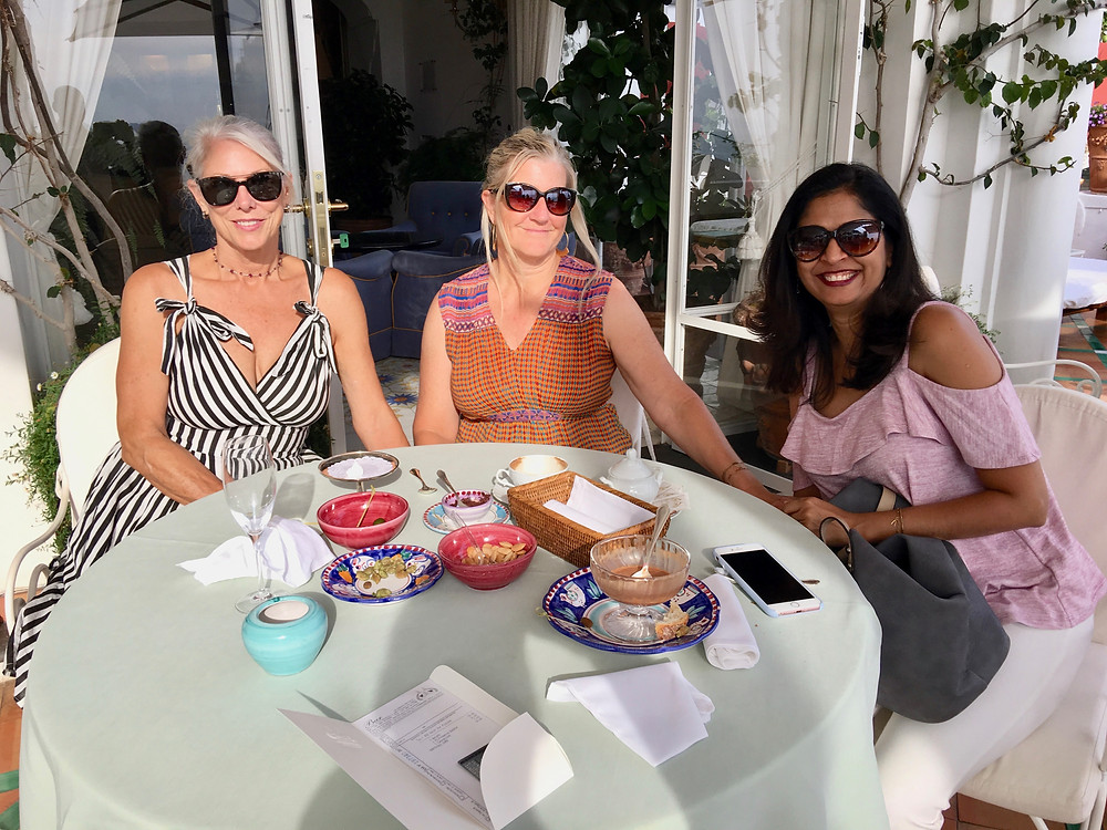 Wander Away with Siri Kay with Katie Bowles and Vaishali Patel of Sanskar Teaching sitting at a patio table by the pool at Le Sirenuse, Positano Italy