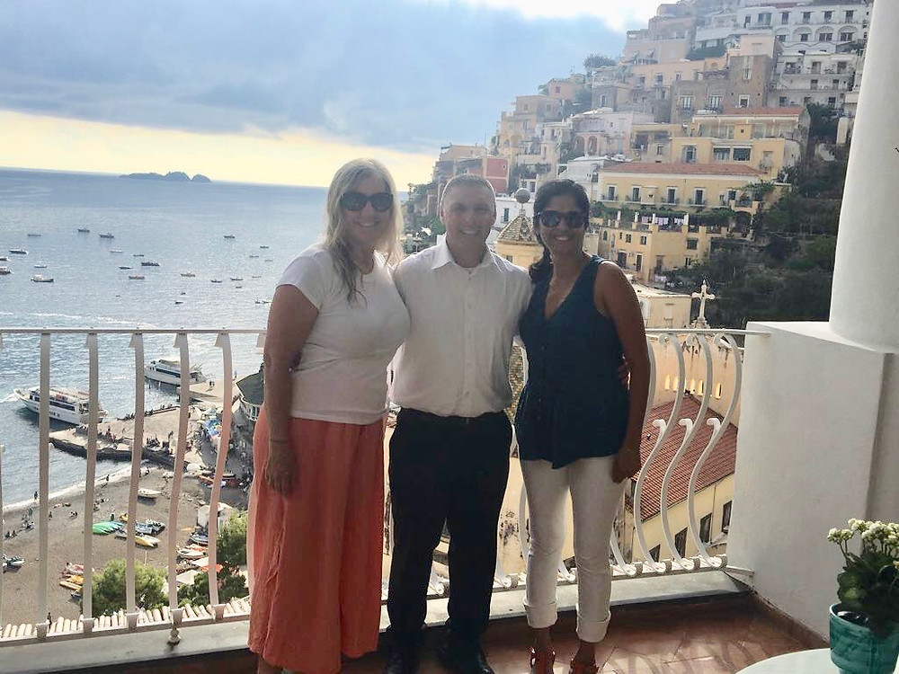 Wander Away with Siri Kay, with Le Sirenuse waiter and Vaishali Patel of Sanskar Teaching on the poolside bar terrace overlooking Positano, italy