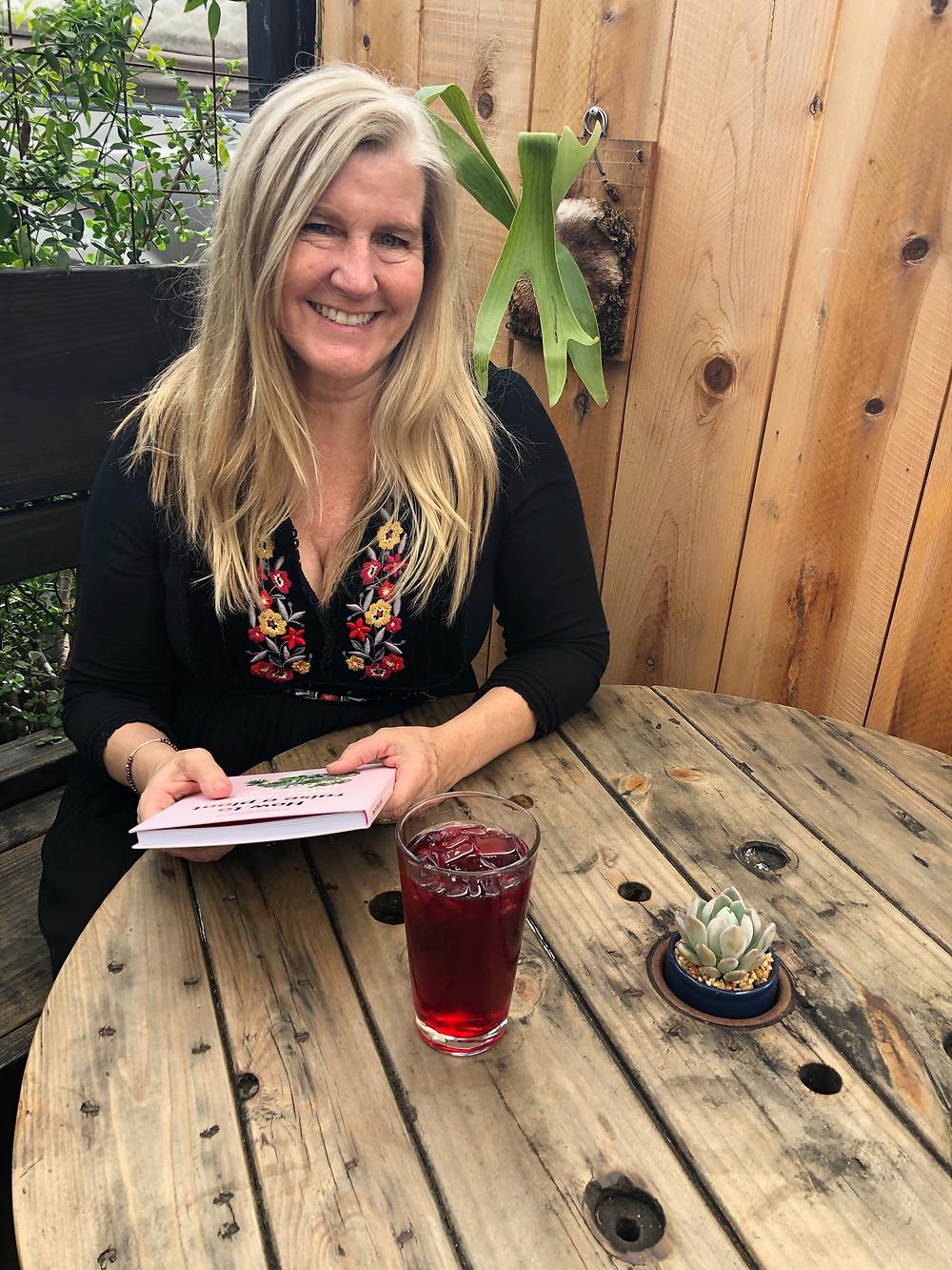 Siri Kay Jostad of Wander Away with Siri Kay sitting on the patio at OB Beans Coffee Roasters in Ocean Beach San Diego California
