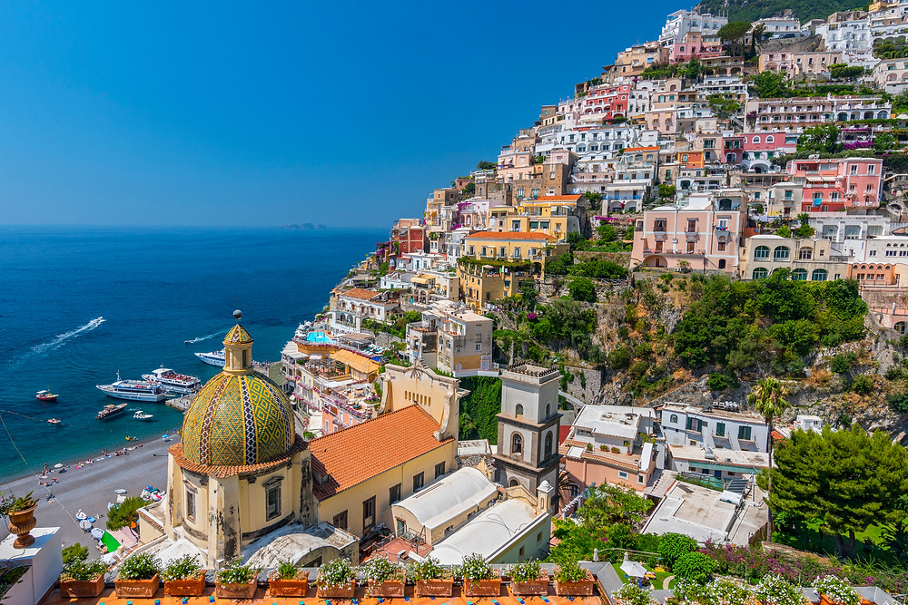 view of the beach and church in Positano Italy as seen from the hillsides