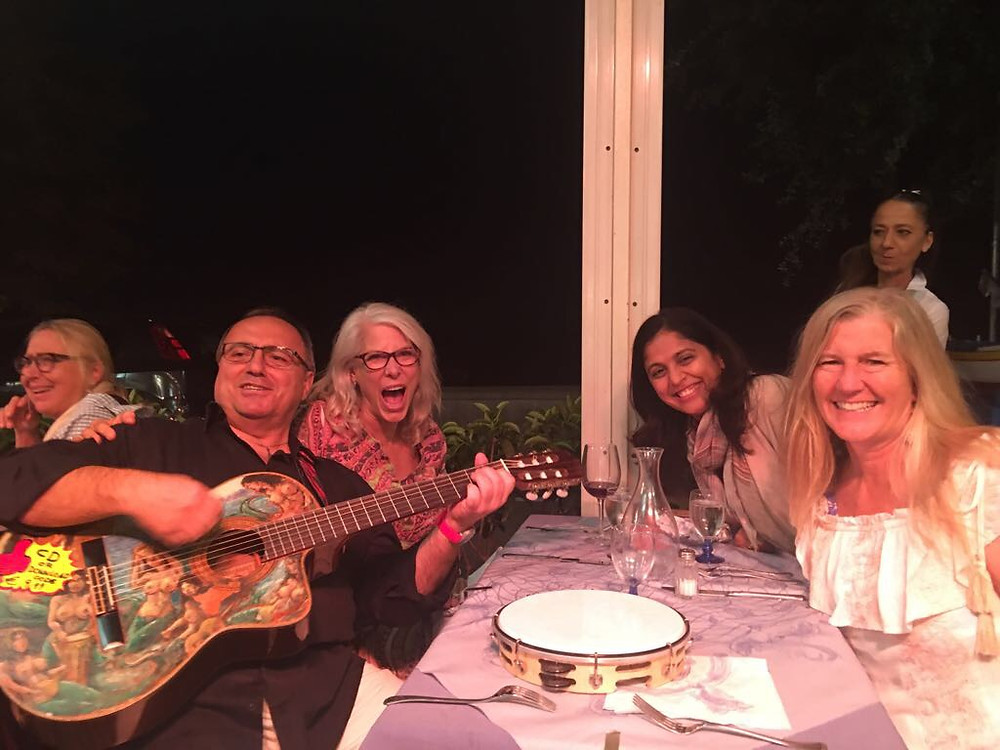 Guitarist, Pietro Rainone singing on the patio of Ristorante Mediterraneo, Positano Italy with Wander Away with Siri Kay, Katie Bowles and Vaishali Patel of Sanskar Teaching