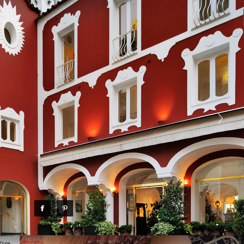 Entrance to the Le Sirenuse Hotel in Positano Italy.  The hotel is marked by its signature red paint with white trim.