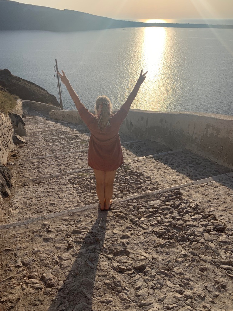 Siri Kay Jostad of Wander Away with Siri Kay back turned to the camera arms up giving the peace sign to the caldera view and the sunset from the stairs down to Ammoudi Bay in Oia Santorini Greece