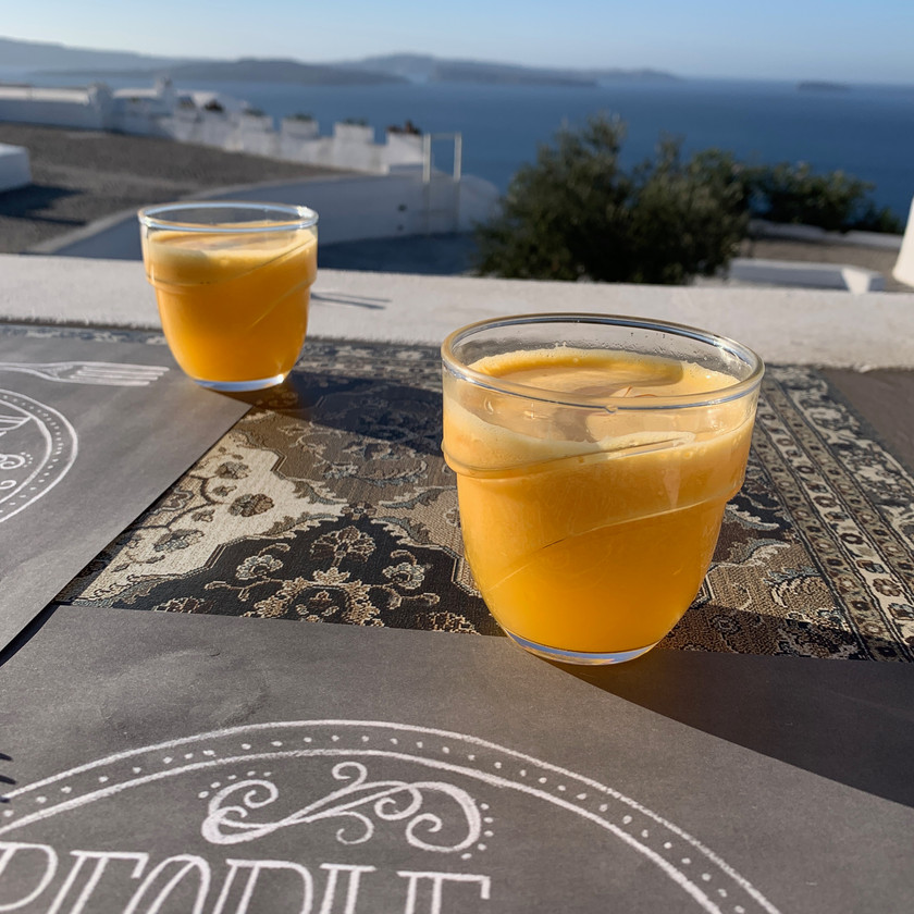 Fresh Squeezed orange juice with a view of the caldera Entrance to Passaggio Bites and drinks in Oia Santorini Greece