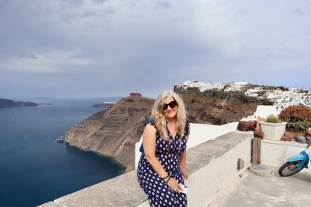 Siri Kay Jostad of Wander Away with Siri Kay sitting on a wall with a view of the caldera in Santorini Greece