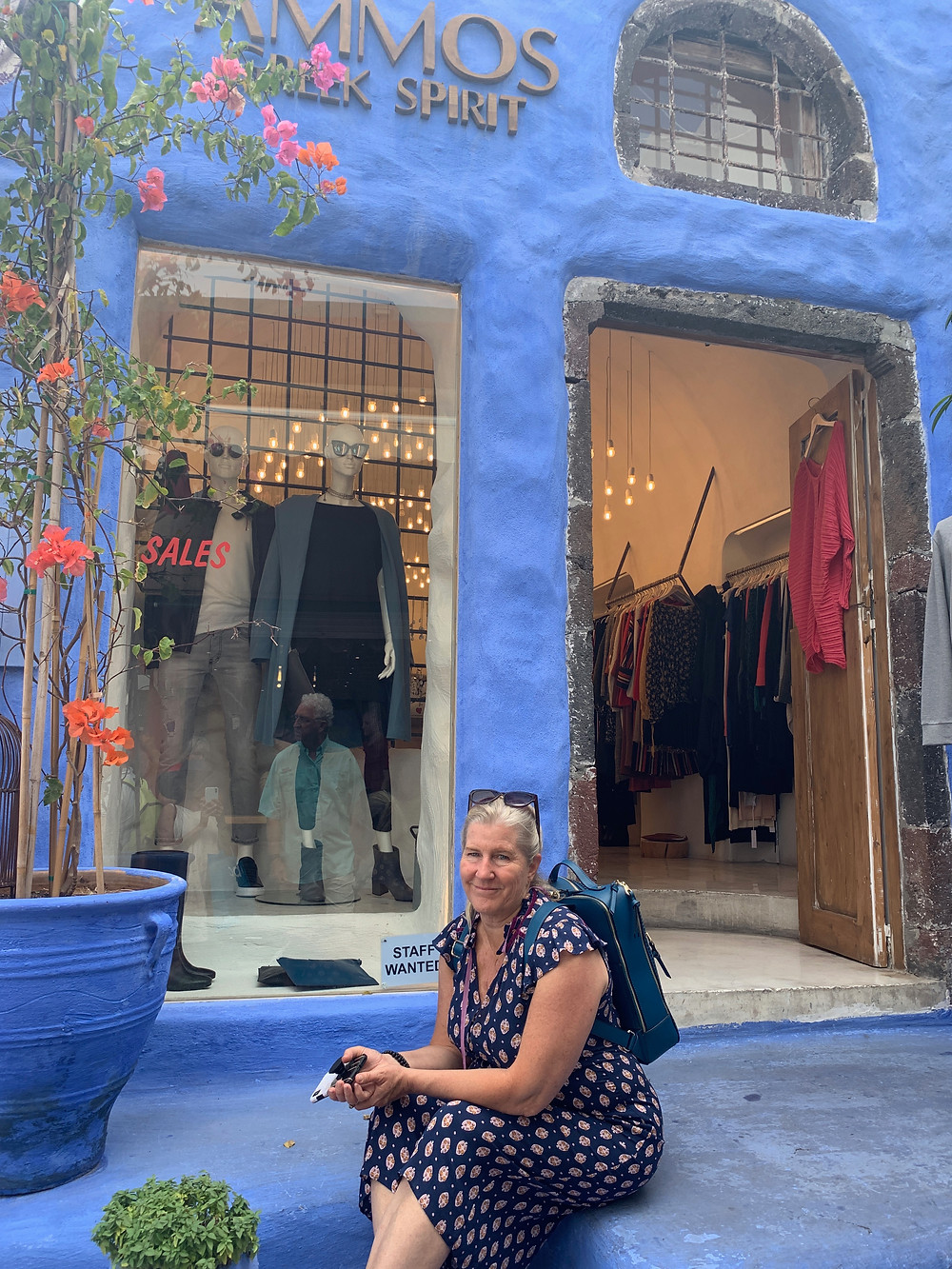 Siri Kay Jostad of Wander Away with Siri Kay sitting in front of a shop in Fira Santorini Greece