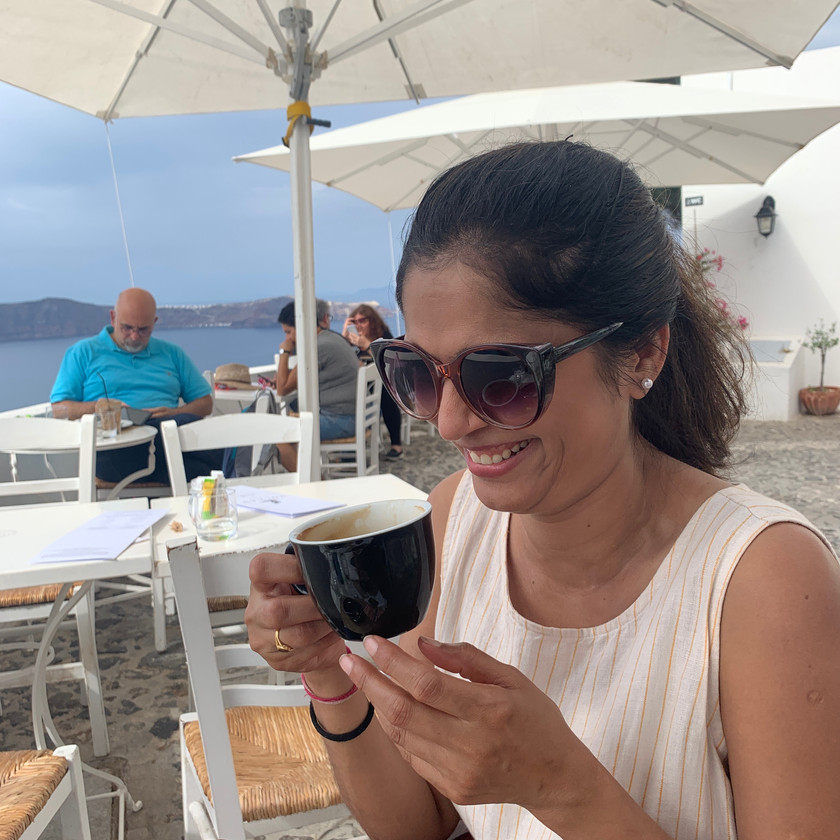 Vaishali Patel of Sanskar Teaching drinking coffee and laughing at Ergon Restaurant in Firostefani Santorini Greece