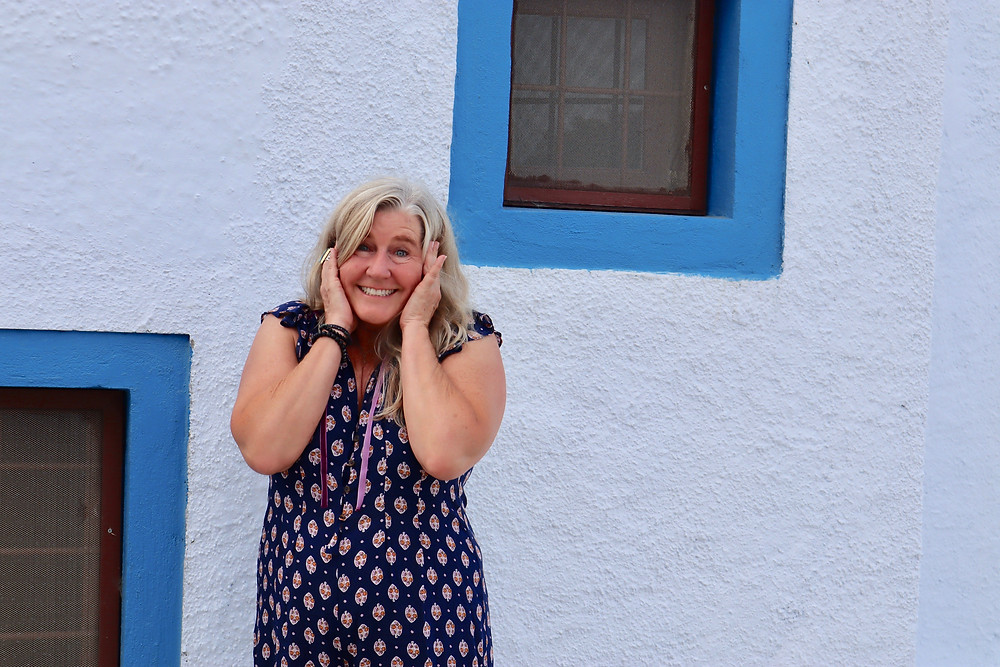 Siri Kay Jostad of Wander Away with Siri Kay holding her hands to her ears, shoulders scrunched up with joy standing in front of blue and white Greek Church on the path between Oia and Fira in Santorini Greece