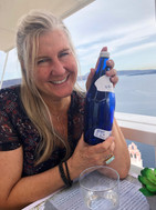 Siri Kay Jostad of Wander Away with Siri Kay holding a blue glass water bottle at Pelekanos Restaurant in Oia Santorini Greece.  There is the caldera view in the background