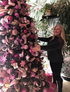 Siri Kay Jostad of Wander Away with Siri Kay hugging a pink christmas tree at Holy Matcha in San Diego California