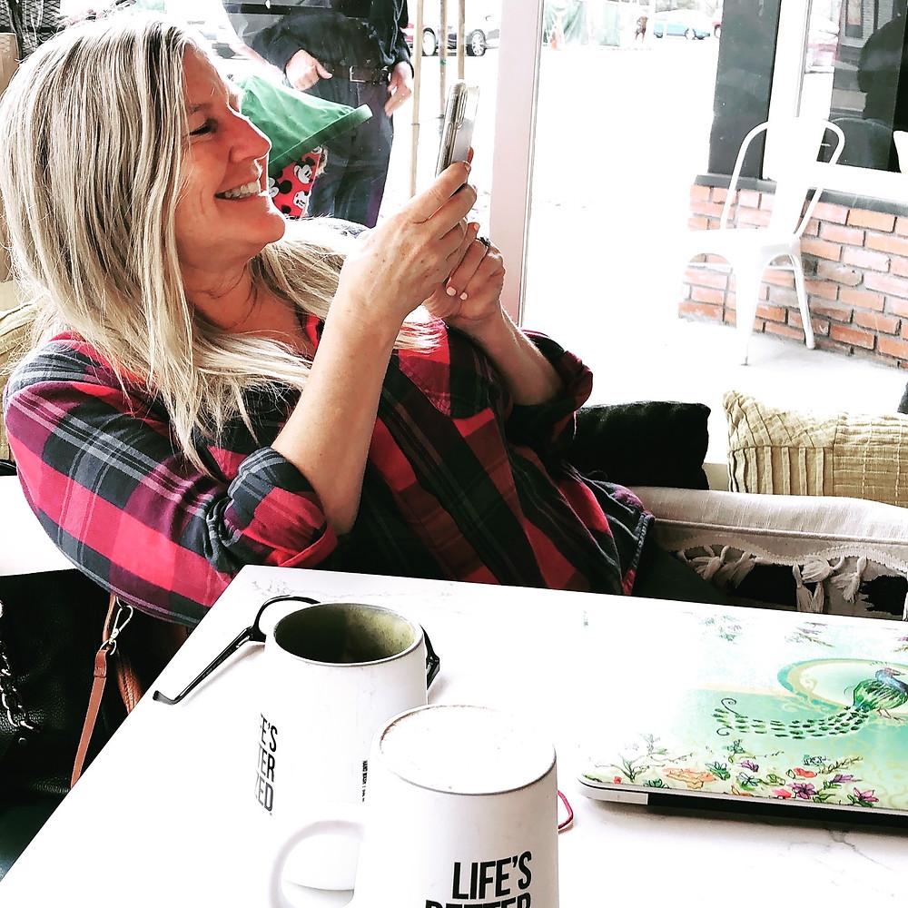 Siri Kay Jostad of Wander Away with Siri Kay taking a photo at Better Buzz Coffee in Hillcrest San Diego California