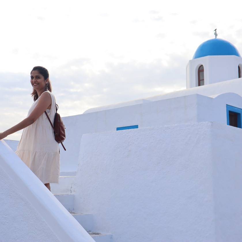 Vaishali Patel of Sanskar Teaching on stairs of a blue and white Greek church on the trail between Oia and Fira in Santorini Greece