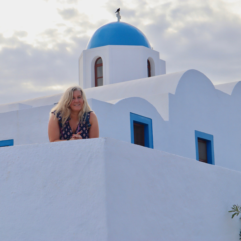 Siri Kay Jostad of Wander Away with Siri Kay on deck of a blue and white Greek church on the trail between Oia and Fira in Santorini Greece
