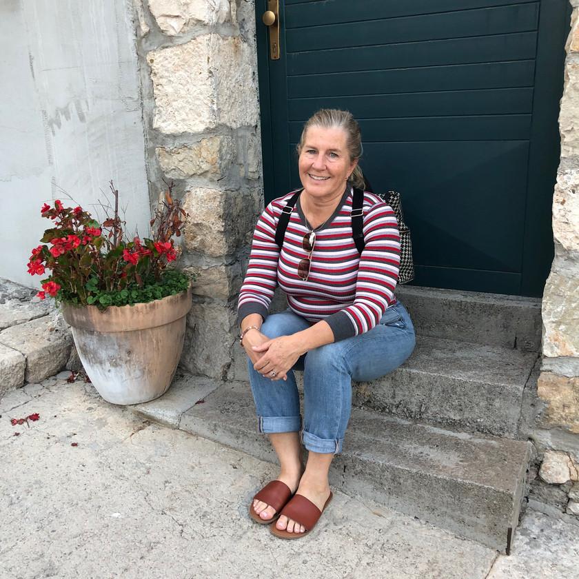 Siri Kay Jostad of Wander Away with Siri Kay resting on stone steps in Split Croatia