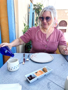 Siri Kay Jostad of Wander Away with Siri Kay pouring water from a blue glass water bottle at Roka Restaurant in Oia Santorini Greece