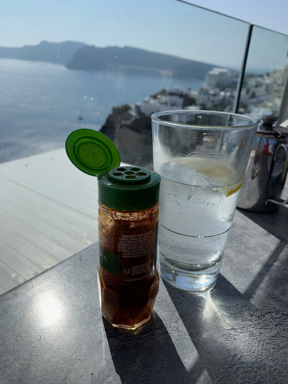 Achaar masala on a table with a view of the caldera in Oia Santorini Greece