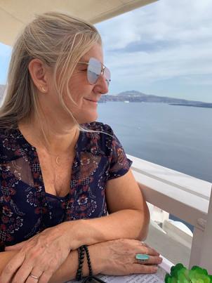 Siri Kay Jostad of Wander Away with Siri Kay overlooking the caldera view from Pelekanos Restaurant in Oia Santorini Greece