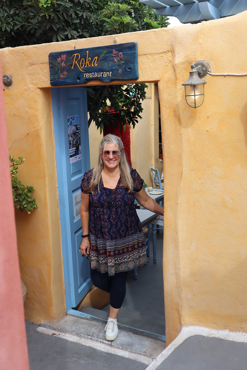 Siri Kay Jostad of Wander Away with Siri Kay standing in the door of Roka Restaurant in Oia Santorini Greece