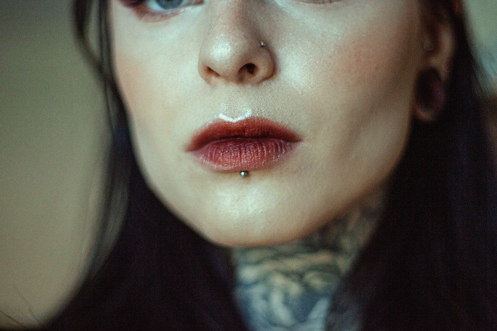 Image of a woman with nose and lip piercings