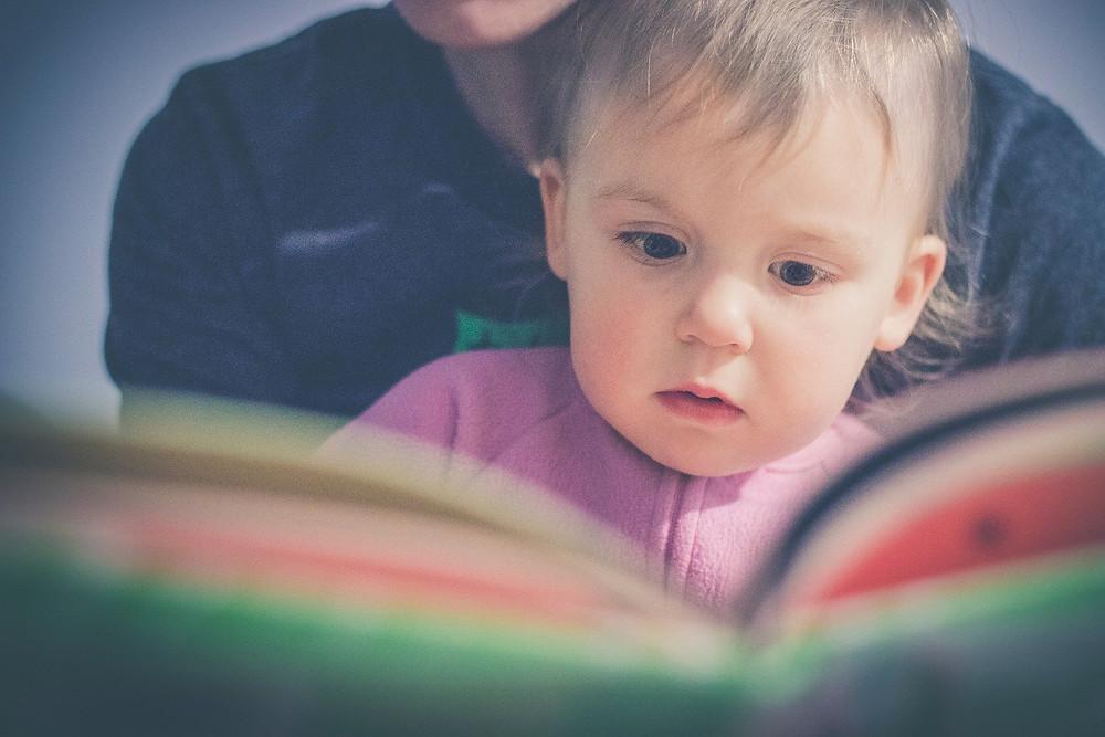 Maria Montessori donnait une grande importance aux livres, notamment pour favoriser l'apprentissage du langage et cela a été confirmé par des études plus récentes. On peut commencer à donner des livres aux plus petits, en commençant par des livres solides et en noir et blanc. L'enfant, qui ne distingue pas encore les couleurs est attiré par les contrastes et cela va l'aider à faire travailler sa vision. Il est aussi attiré par les visages, on peut proposer un album avec des photos de famille, ou encore des visages très expressifs pour introduire les émotions.