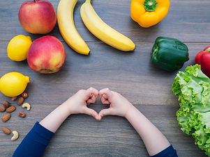 Kid making heart shape with her hands and healthy food on the table, top view