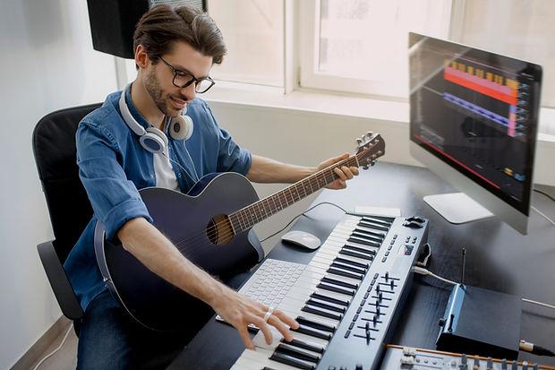 Man plays guitar and produce electronic