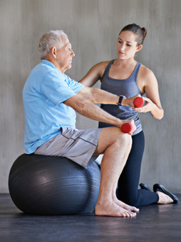 woman assisting older man on exercise ball while holding weight