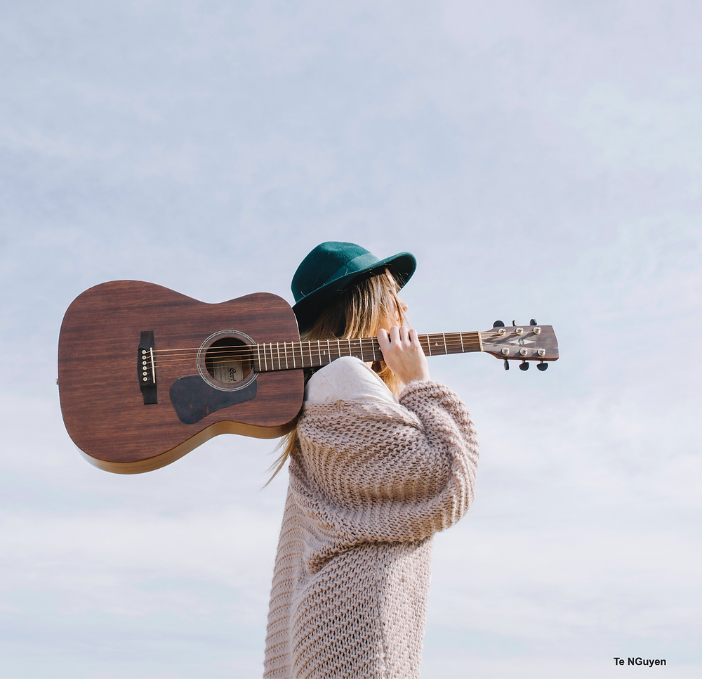 Female holding a guitar over her shoulder with background of blue sky