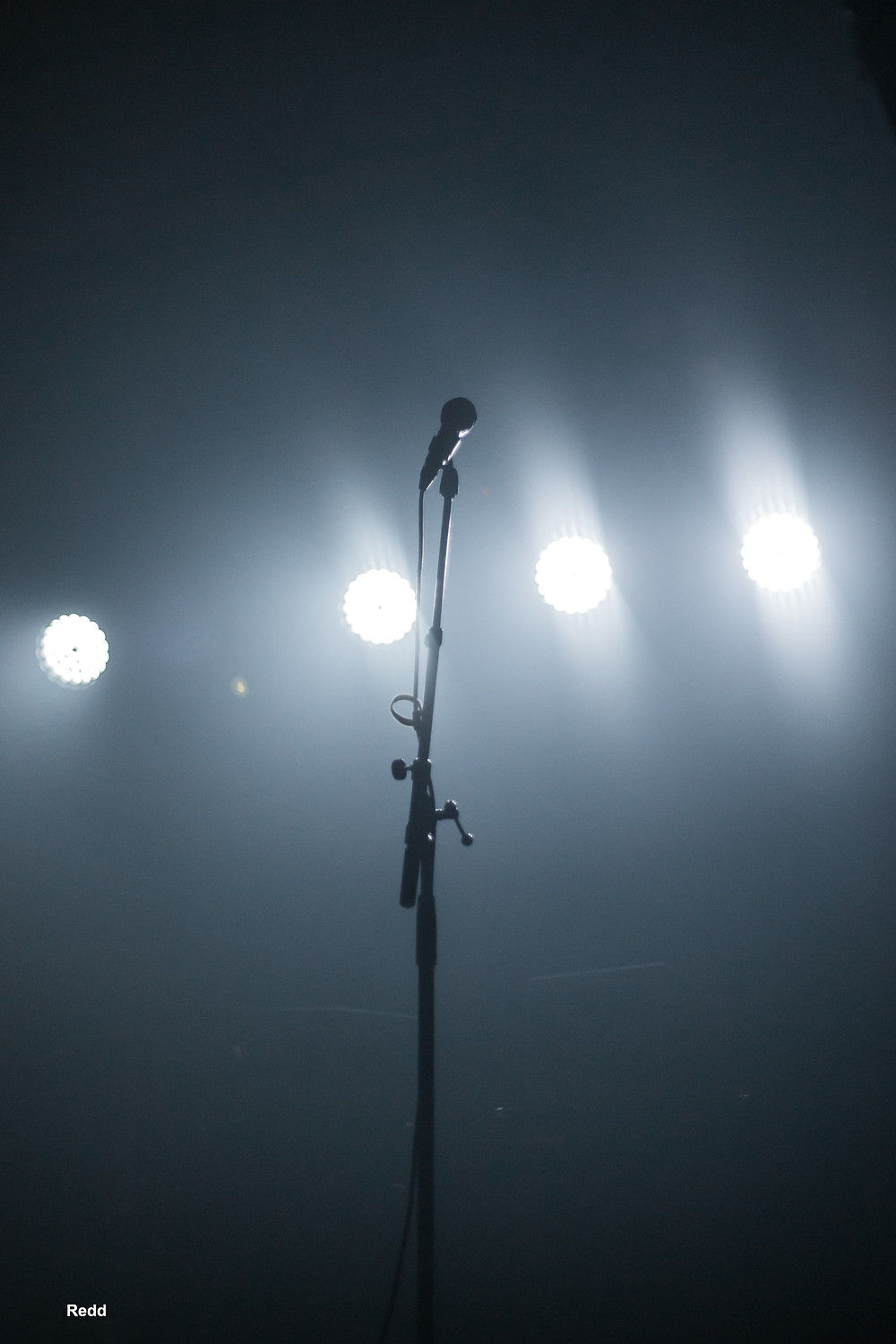 Black and White silhouette of a backlit microphone on stage