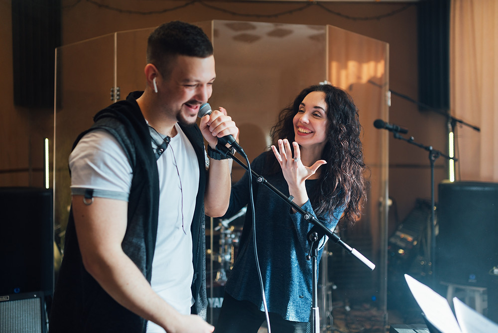 male singer being coached by a female voice coach