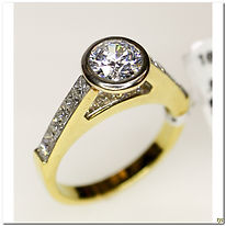 This designer ring is created by Mastini. It was created in 18 karat two-tone. This semi-mount setting will support an 1 carat diamond that is bezel set in this floating setting. Currently is set with a CZ for display purposes.
