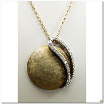 This designer pendant is created by Breuning.  It is made in 14 karat two-tone. A slight textured dome in yellow with a loop of diamonds totaling .17 carats total weight of SI clarity.