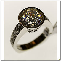 This designer ring is created by Caressa. It is made in 18 karat white gold with .80 carat total weight of diamonds. The center mounting will support a 2 carat stone and is currently set with a cubic zirconia for display purposes. Two rows of diamonds flank either side of the band about half way down as well as under the bezel mounting. It also comes with a Euro shank to help prevent the ring from twisting on the finger.