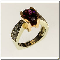 This designer ring is created by Frank Ruebel. It features a 2 carat rubelite tourmaline center gemstone. It also supports 18 diamonds that have a total weight of .28 carats. It is made of 14 karat rose and white gold.
